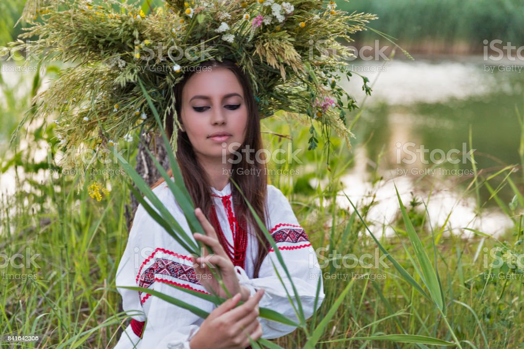 Beautiful girl in embroidery shirt and wreath of wild flowers. stock photo
