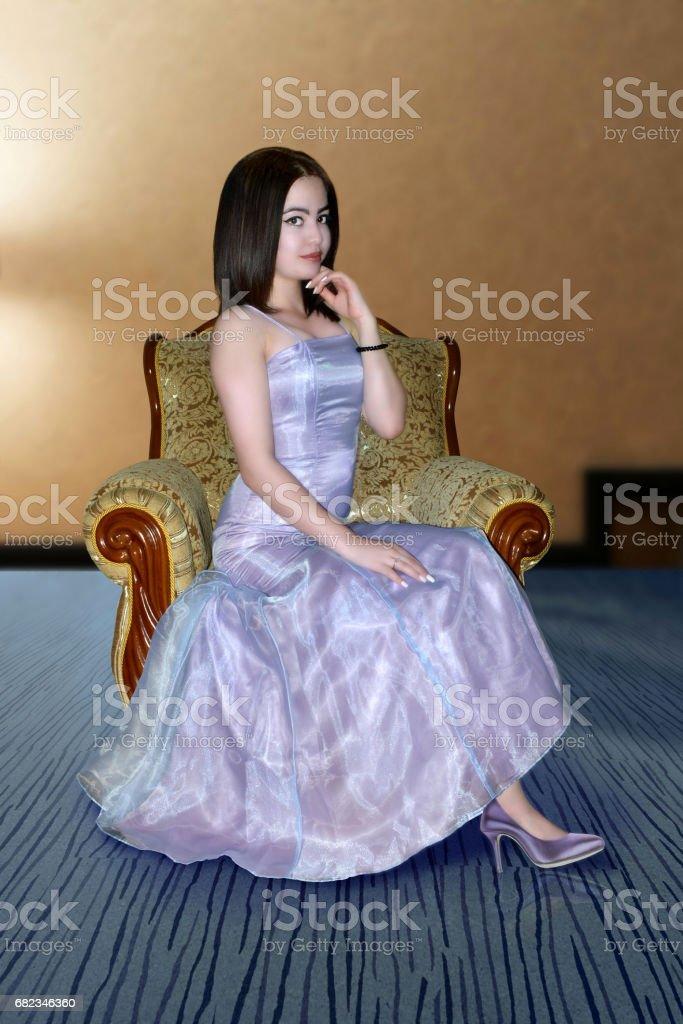 vacker flicka i kväll lila klänning i fåtölj royaltyfri bildbanksbilder