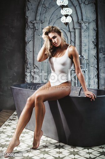 Beautiful girl in fashion clothes posing at grey background. Photo of beautiful girl with slim toned body. Beauty and body care concept