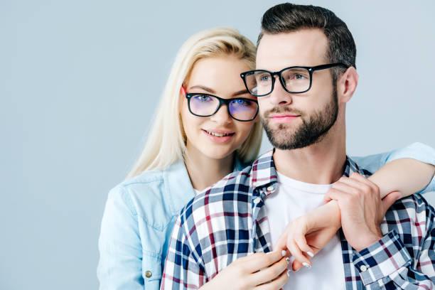 schöne mädchen in brille umarmen mann isoliert auf grau - brille stock-fotos und bilder