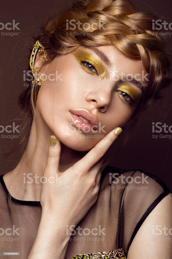 Beautiful girl in gold dress with creative makeup and braids stock photo