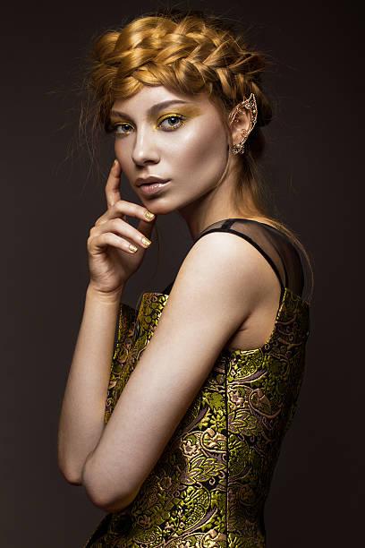 schönes mädchen in gold kleid mit kreativen make-up und geflochtener zopf - elfenkostüm damen stock-fotos und bilder