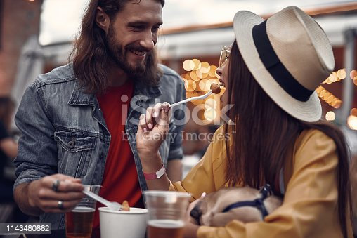 Portrait of young hipster couple having fun in outdoor cafe. Cheerful lady eating with fork and holding sleeping pug dog while bearded man staring at her with smile