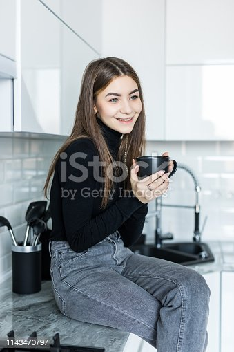 Beautiful blonde girl in home clothes is using a smartphone and smiling while sitting in kitchen