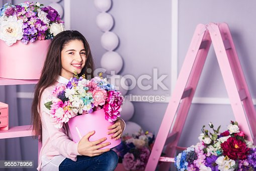 961500822 istock photo Beautiful girl in jeans and pink sweater in studio with decor of flowers in baskets. 955578956