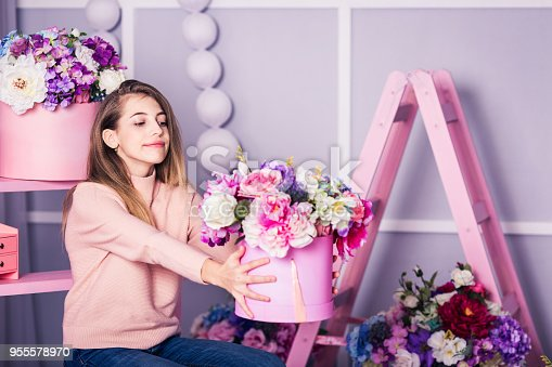 961500822istockphoto Beautiful girl in jeans and pink sweater in studio with decor of flowers in baskets. 955578970