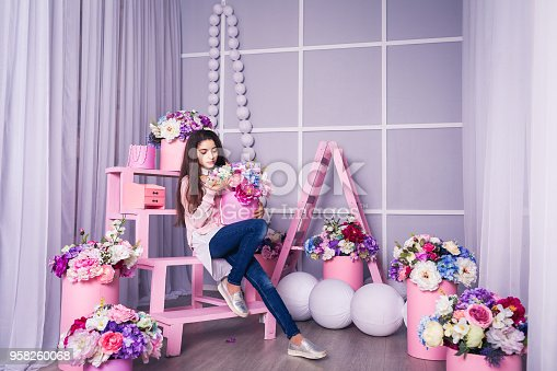 961500822 istock photo Beautiful girl in jeans and pink sweater in studio with decor of flowers in baskets. 958260068