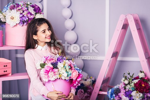 istock Beautiful girl in jeans and pink sweater in studio with decor of flowers in baskets. 958260070