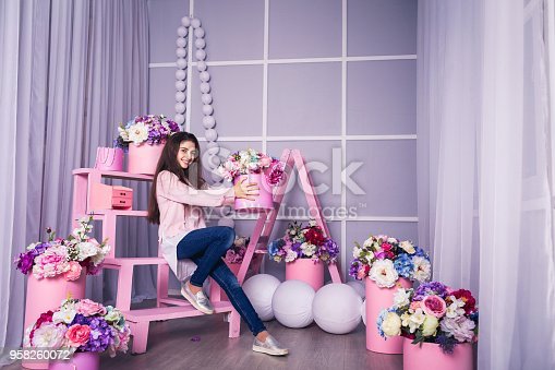 961500822 istock photo Beautiful girl in jeans and pink sweater in studio with decor of flowers in baskets. 958260072