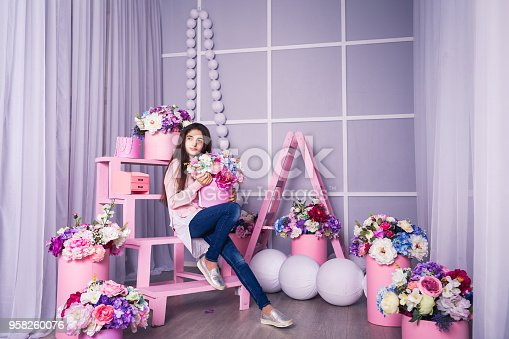 961500814istockphoto Beautiful girl in jeans and pink sweater in studio with decor of flowers in baskets. 958260076