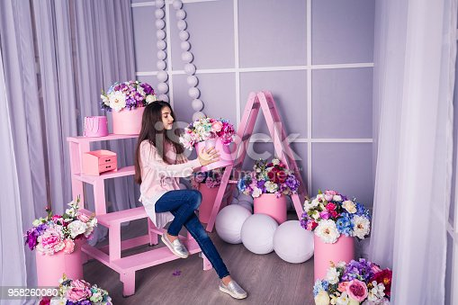 961500822 istock photo Beautiful girl in jeans and pink sweater in studio with decor of flowers in baskets. 958260080