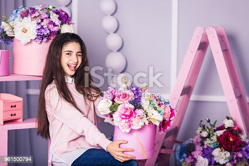 961500822 istock photo Beautiful girl in jeans and pink sweater in studio with decor of flowers in baskets. 961500794