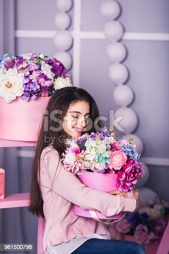 961500822 istock photo Beautiful girl in jeans and pink sweater in studio with decor of flowers in baskets. 961500798