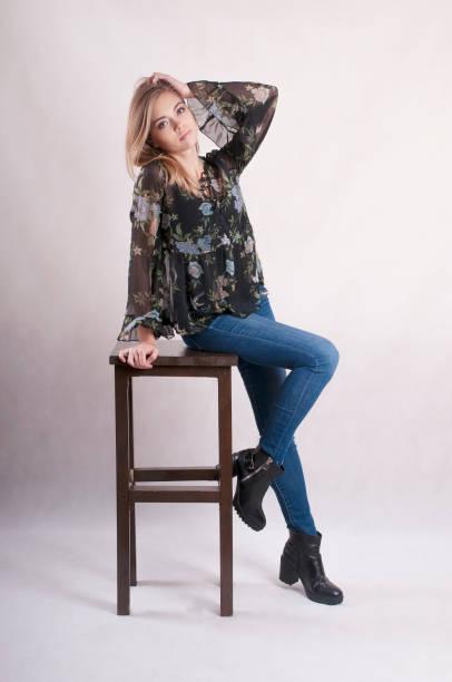 schönes mädchen in jeans sitzt auf einem hohen stuhl-studio - modedetails stock-fotos und bilder