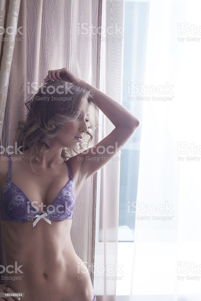 Beautiful girl in lingerie posing at window royalty-free stock photo