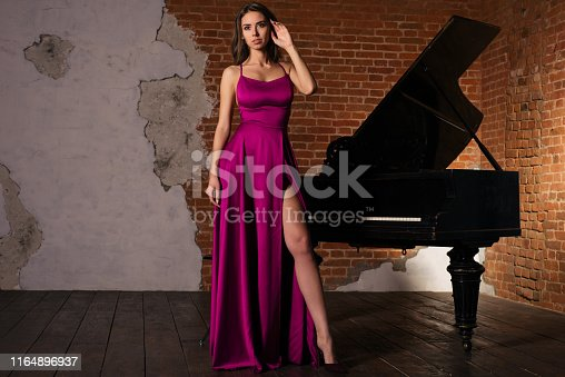Beautiful girl in long classic red dress posing with old piano. - image
