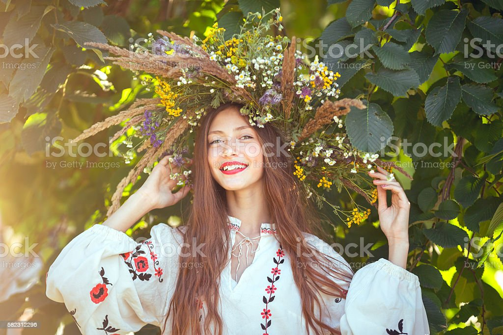 Beautiful girl in meadow in national suite beautiful girl in wreath of flowers in meadow on sunny day. Portrait of Young beautiful woman wearing a wreath of wild flowers. Young pagan Slavic girl conduct ceremony on Midsummer. Earth Day Adult Stock Photo