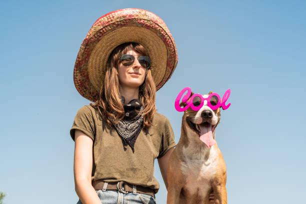 schönes mädchen in mexikanischen hut verkleidet als bandit gangsters mit hund in coole sonnenbrillen - coole halloween kostüme stock-fotos und bilder