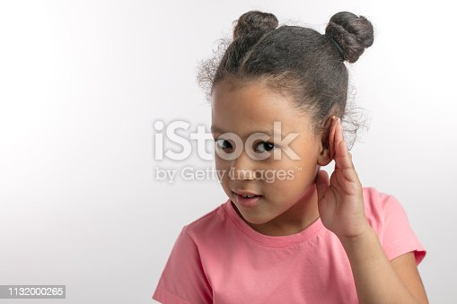 beautiful girl with dark hair in pink fashon dress is listening with her hand on an ear.copy space. isolated white background. hearing concept