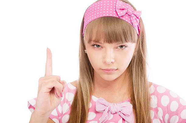 Beautiful girl in pink lifts finger up stock photo