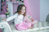 Beautiful girl in pink pants sits on a sofa. A child in a home interior in the room looks into the camera and smiles
