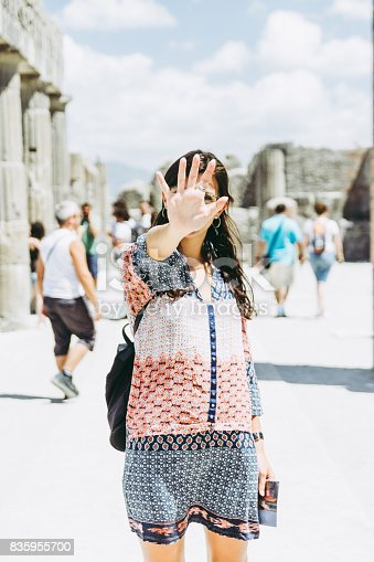 860524946 istock photo Beautiful girl in Pompei, Naples, Italy, cover her face with the right hand. 835955700