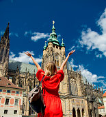 Beautiful girl in red dress travel in Prague, Church on background
