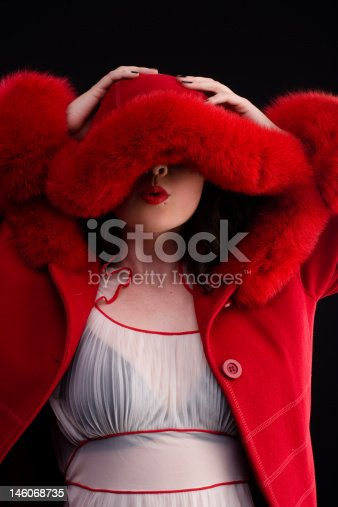 beautiful girl in red fur coat blowing a kiss on black background