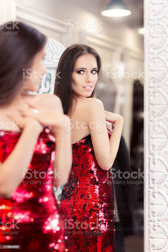 Beautiful Girl in Red Sequin Dress Looking in the Mirror stock photo