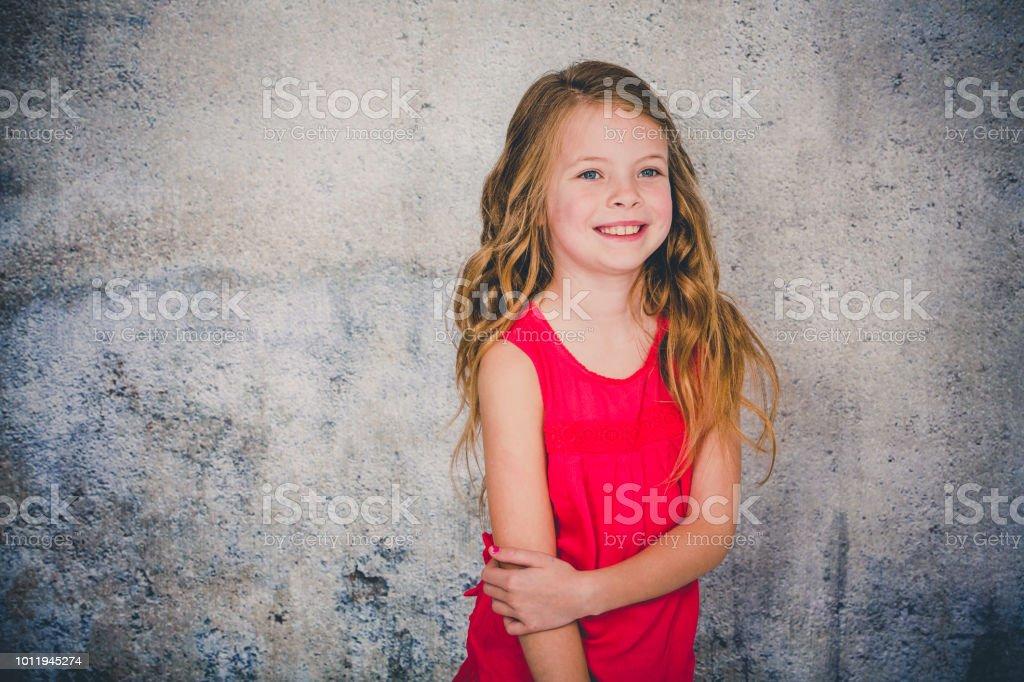 schönes Mädchen in rotem Hemd vor konkreten Hintergrund posiert und zeigt – Foto