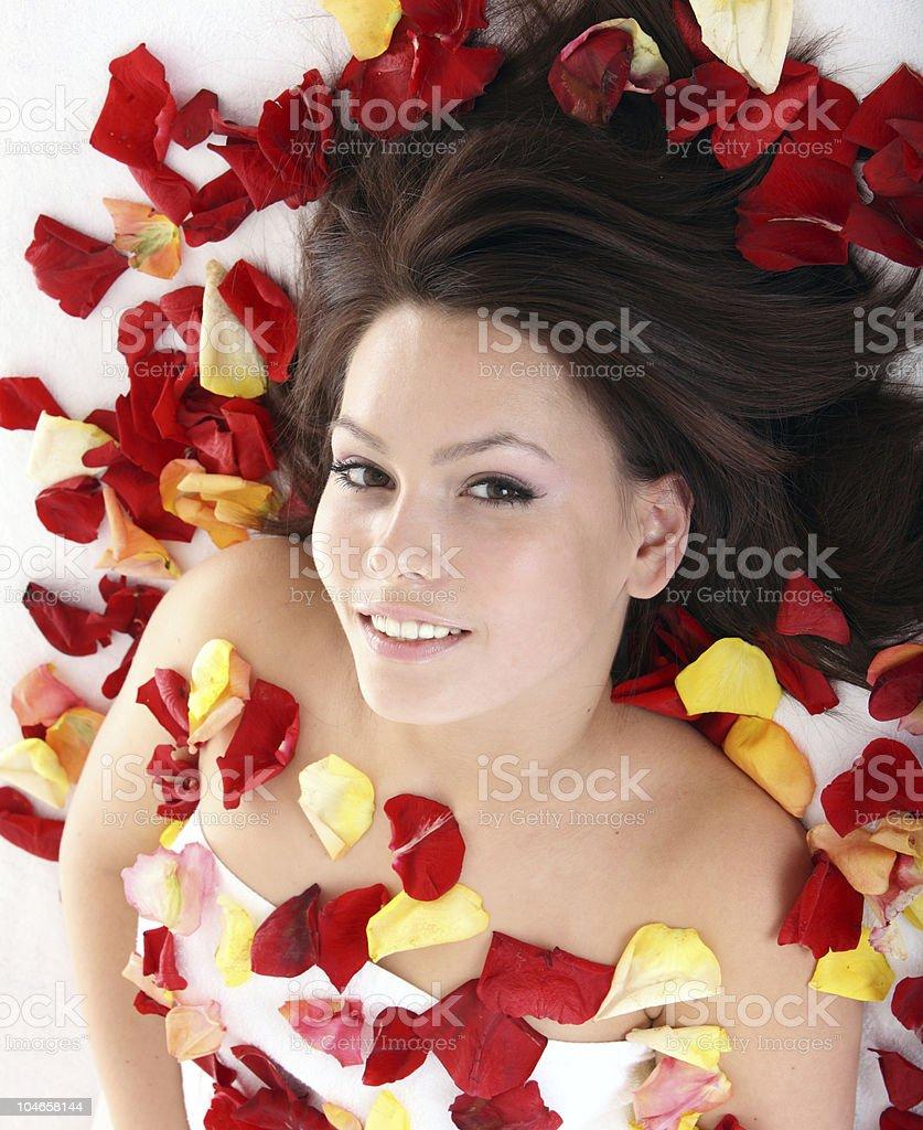 Beautiful girl in rose petal. Spa. royalty-free stock photo