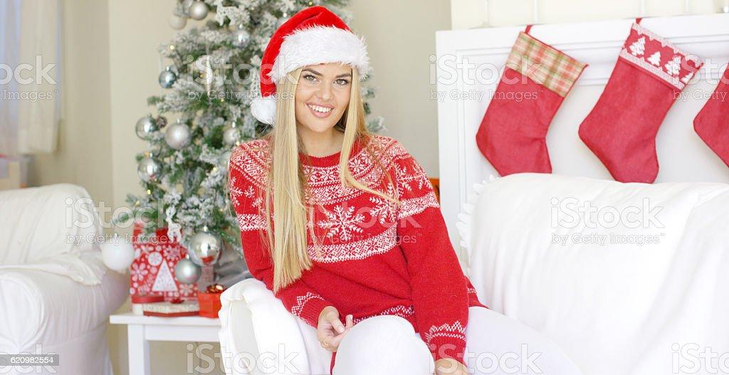 Beautiful girl in Santa Claus hat in her living room foto royalty-free