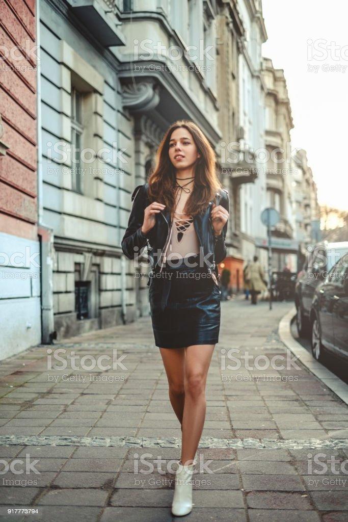 Garota linda saia com mochila andando na calçada - foto de acervo