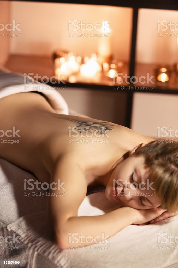 Beautiful girl in spa salon on candle background stock photo