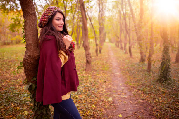 beautiful girl in stylish fall fashion clothes in park scenery, in nice warm autumn sunlight. gorgeous romantic young woman outdoors. american plan shot in natural light, retouched, vibrant colors - fall fashion stock photos and pictures