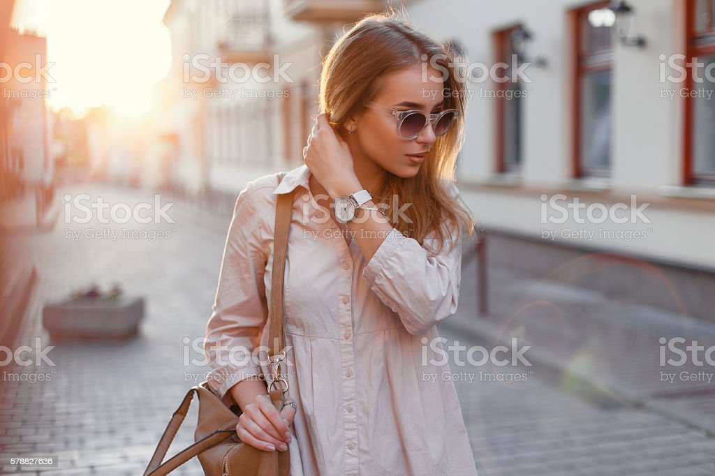 Beautiful girl in stylish sunglasses and with bag at sunset. stock photo