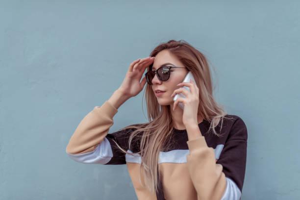 schöne mädchen im sommer in der stadt, telefonieren, hintergrund graue wand, schwarz und beige pullover strickjacke, ein handy hört nachricht in internet-anwendung online. lange haare sonnenbrille. - wortarten bestimmen übungen stock-fotos und bilder