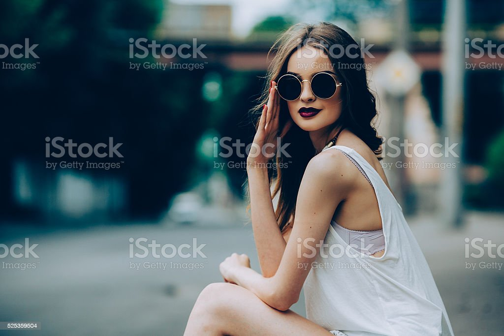 beautiful girl in sunglasses sitting stock photo