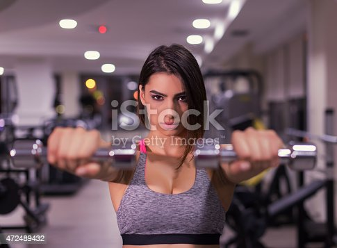 Beautiful girl in the gym working out, shallow dof with blurred background