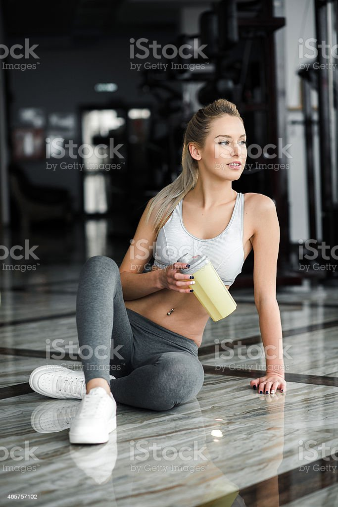 Beautiful girl  in the gym with a yellow shaker. stock photo
