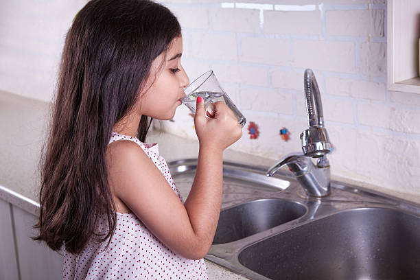 beautiful girl in the nice white kitchen (series) - tap water stok fotoğraflar ve resimler