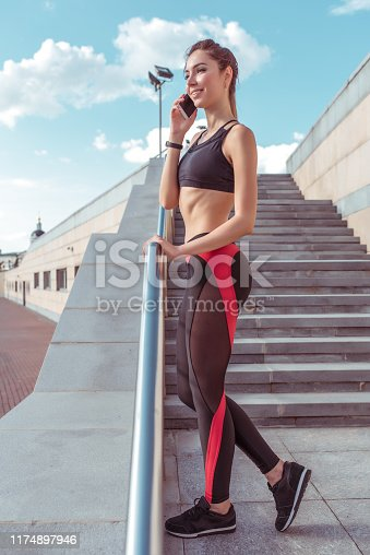Beautiful girl in top sports leggings, phoning, happy smiling, resting after summer workout in city on jogging morning, active youth lifestyle. Fitness walk, workout, slim tanned figure