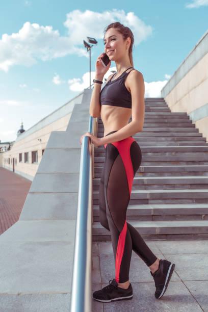 schöne mädchen in top-sport-leggings, telefonieren, glücklich lächeln, ruhe nach sommer-training in der stadt an einem jogging-morgen, aktive jugend-lifestyle. fitness-spaziergang, workout, schlanke gebräunte figur - wortarten bestimmen übungen stock-fotos und bilder