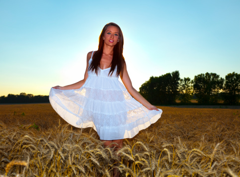 Beautiful Girl In Wheat Field Backlit By Setting Summer Sun Stock Photo - Download Image Now