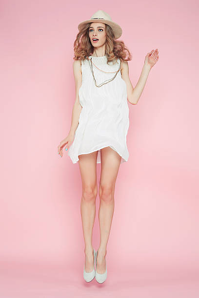Beautiful girl in white clothes posing on pink background stock photo