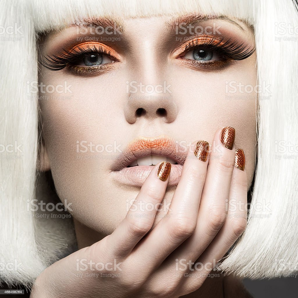 Beautiful girl in white wig, with gold makeup and nails. stock photo