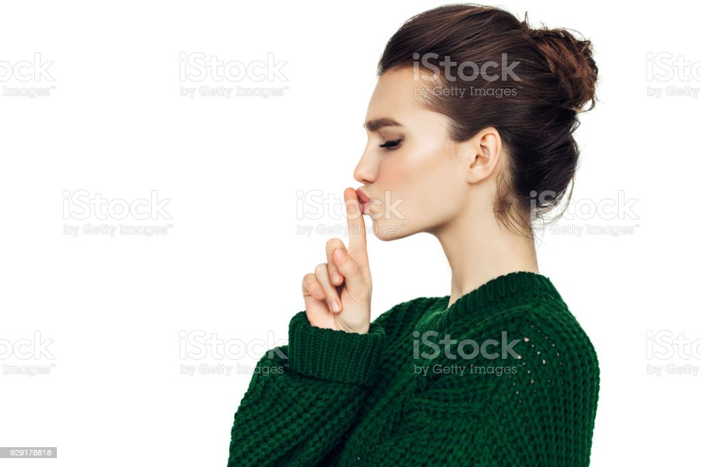Beautiful girl indicates to be quieter stock photo