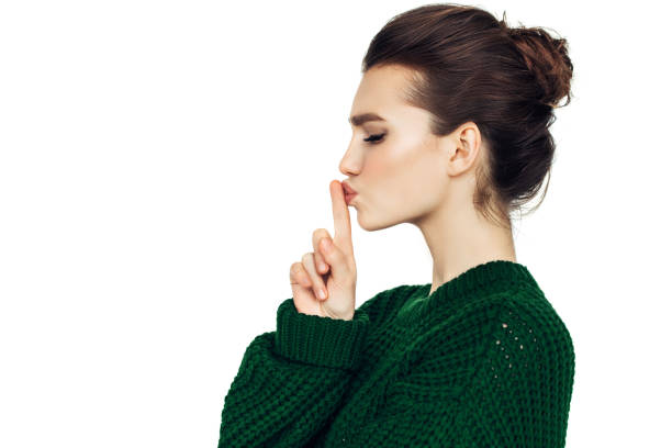Beautiful girl indicates to be quieter Beautiful girl indicates to be quieter finger on lips stock pictures, royalty-free photos & images