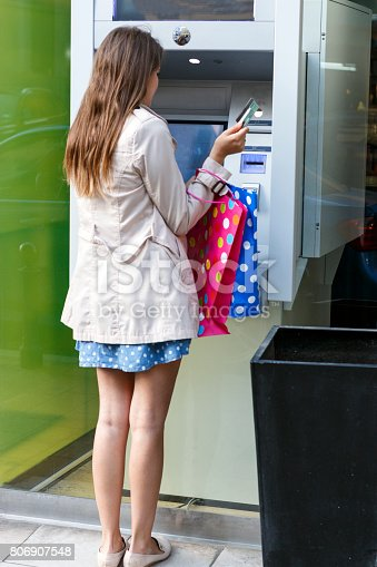 945598452istockphoto Beautiful girl inserting a credit card to ATM machine 806907548