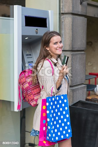 945598452 istock photo Beautiful girl inserting a credit card to ATM machine 806912040